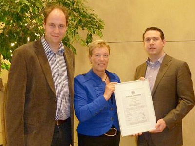 Overhandiging van NTA 8080 certificaat door dhr. J. Bronsvoort, Managing Director Quality Services Certification BV, aan mevr. Kwast en dhr. Wennemers van Bruins & Kwast
